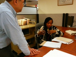Archivist Vince Lee (left) and Chinwendu Rose Ejezie discuss the Toni Beauchamp Papers