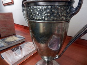 closeup, showing the detail on the loving cup, inscription reads:  Presented By / Directors of No-tsu-oh Ass'n / To / Thomas Flaxman / V.P. & Genl. Mgr. / Deep Water Jubilee / Nineteen Fourteen