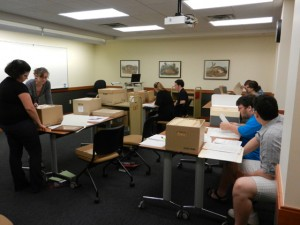 Students in the Archival Practice and Organizational Histories course meeting in the Evans Room of Special Collections.