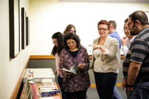 Attendees and panelists mingle, discuss, and view some of Mena's works at last months event.    Additional photos of the event can be viewed here. (Photo courtesy of Mauricio Lazo, University of Houston Libraries.)