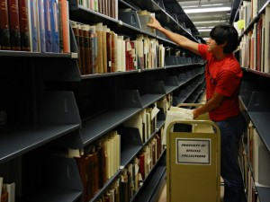 Uribe assists with a project to consolidate space, shifting books in our secure stacks area