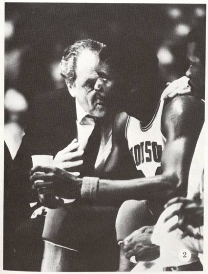 "1984:  Coach Lewis and Hakeem Olajuwon talk strategy. (Houstonian).  In the early 1980s Texas' Tallest Fraternity is born as ""Akeem"" Olajuwon, Clyde Drexler, Michael Young, and the rest of Phi Slama Jama help propel the Cougars to three straight Final Four appearances from 1982 to 1984.  Lewis championed their up-tempo, above-the-rim style noting that slam dunks (once outlawed in college basketball) are ""high-percentage shots."""