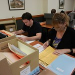 Students looking through a box of documents from the River Oaks Business Women's Exchange Club Records.